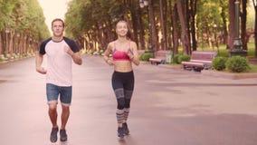 美丽的训练奔跑在公园,慢动作的女孩和人 影视素材