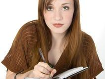 美丽的记事本红头发人青少年的文字 免版税图库摄影
