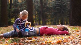 美丽的说谎在草的妈妈和逗人喜爱的孩子在秋天公园 女儿坐妈妈并且吃香蕉,对天空的妈妈神色 股票视频