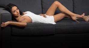 美丽的说谎在长沙发的妇女佩带的白色礼服 免版税库存图片