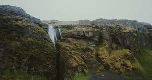 美丽的谷的鸟瞰图与河的 飞行在Gljufrabui瀑布的直升机在山之间在冰岛 股票视频