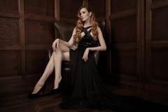 美丽的豪华妇女坐一把皮革葡萄酒椅子 免版税库存图片