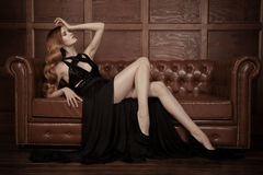 美丽的豪华妇女坐一皮革vi 库存照片