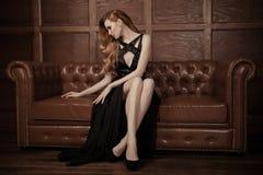 美丽的豪华妇女坐一皮革vi 库存图片