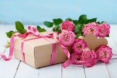 美丽的贺卡为生日、妇女或者母亲节 桃红色玫瑰开花和有丝带的礼物盒在绿松石桌上 淡色 免版税库存照片