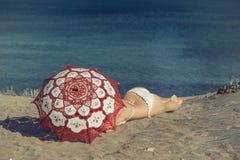 美丽的赤裸女性在海滩说谎在一把红色伞下 沙子的女孩在伞下 免版税库存图片