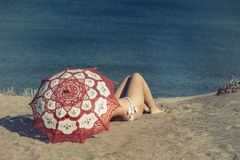 美丽的赤裸女性在海滩说谎在一把红色伞下 沙子的女孩在伞下 库存照片