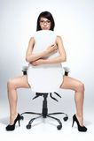 美丽的赤裸深色头发的妇女坐白色椅子 免版税库存图片