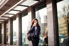 年轻美丽的走在城市附近的浅黑肤色的男人饮用的咖啡 皮夹克,都市背包,明亮的红色嘴唇 库存图片