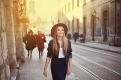年轻美丽的走在老城市的妇女佩带的帽子画象  街道时尚概念 定调子 免版税库存照片