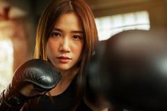 美丽的运动亚裔与把G装箱的拳击手妇女沙袋 库存照片