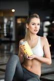 美丽的运动女孩在与一台黄色振动器的健身房摆在 免版税库存照片