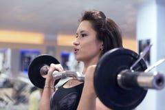 美丽的运动的女孩培养在健身房的杠铃 修造muscl 免版税库存照片
