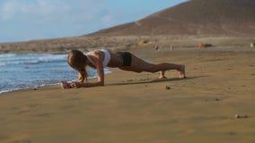 美丽的运动的妇女侧视图板条位置的在日落期间的海滩 影视素材