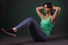 美丽的运动的妇女,做在黑暗的背景的健身妇女锻炼与绿色背后照明 库存照片