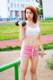 美丽的运动的红发女孩向在街道的体育求助有金属哑铃的 免版税图库摄影