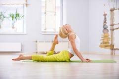 美丽的运动的适合信奉瑜伽者妇女在健身屋子实践瑜伽说谎的asana Ardha Bhujangasana 库存图片