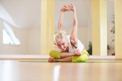 美丽的运动的适合信奉瑜伽者妇女在健身屋子实践瑜伽asana Adho Mukha Agni Stambhasana 库存照片