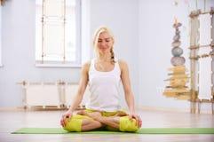 美丽的运动的适合信奉瑜伽者妇女在健身屋子实践瑜伽asana Padmasana -莲花姿势 库存图片