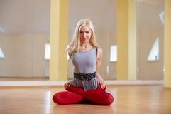 美丽的运动的适合信奉瑜伽者妇女在健身屋子实践瑜伽asana Padmasana -莲花姿势 免版税库存照片