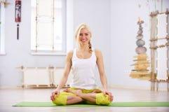 美丽的运动的适合信奉瑜伽者妇女在健身屋子实践瑜伽asana Padmasana -莲花姿势 图库摄影