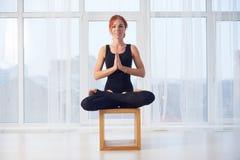 美丽的运动的适合信奉瑜伽者妇女在瑜伽演播室实践瑜伽asana Padmasana -在一个木块的莲花姿势 库存照片