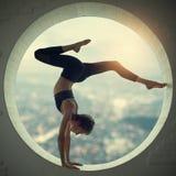 美丽的运动的适合信奉瑜伽者妇女在窗口里实践瑜伽手倒立asana Bhuja Vrischikasana -蝎子手倒立姿势 库存图片