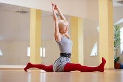 美丽的运动的适合信奉瑜伽者妇女实践瑜伽asana Hanumanasana -在健身屋子胡闹姿势 库存图片