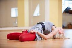 美丽的运动的适合信奉瑜伽者妇女实践瑜伽asana Matsyasana -在健身屋子钓鱼姿势 免版税库存图片