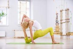 美丽的运动的适合信奉瑜伽者妇女实践瑜伽asana Pigeon国王姿势rajakapotasana在健身屋子 图库摄影