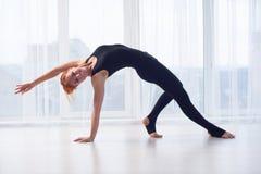 美丽的运动的适合yogini妇女在瑜伽演播室实践瑜伽asana Camatkarasana -狂放的事姿势 库存照片