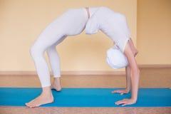 美丽的运动的适合yogini妇女实践瑜伽asana chakrasana (或urdva dhanurasana) 免版税库存图片