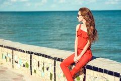 年轻美丽的迷人的时髦的妇女佩带的珊瑚红色连衫裤和黑暗的时髦太阳镜坐栏杆在海边 免版税库存图片