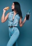 美丽的迷人的纹身花刺女孩用汉堡包和苏打 免版税库存照片