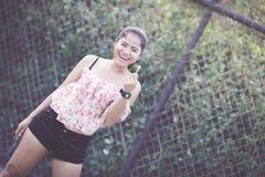 美丽的逗人喜爱的女孩她愉快的面带笑容和她吃点心 免版税图库摄影