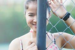 美丽的逗人喜爱的女孩她愉快的面带笑容和她吃点心 免版税库存图片