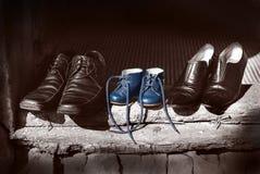 美丽的逗人喜爱的好鞋子家庭父亲母亲穿上鞋子起动和站立在老被佩带的木头的小儿童蓝色颜色老时尚鞋子 图库摄影