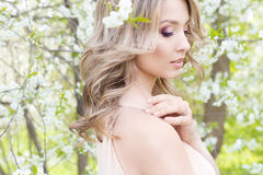美丽的逗人喜爱的嫩年轻白肤金发的女孩在开花的树庭院里在柔和的口气的 免版税库存照片