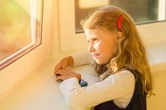 美丽的逗人喜爱的小女孩在看的校服穿戴了  免版税图库摄影