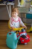 美丽的逗人喜爱的小男孩骑马体育玩具汽车 库存图片