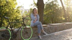 美丽的金发女孩坐长凳在有她迁徙的自行车的城市公园在她旁边 谈话由她 影视素材