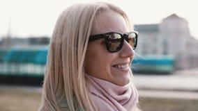 美丽的金发白种人妇女画象  愉快微笑相当时髦的太阳镜侧视图的年轻20s女孩 股票录像