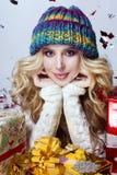 美丽的金发碧眼的女人一个蓝色帽子的女孩有圣诞节礼物的 库存照片