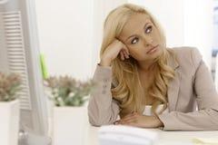 美丽的金发碧眼的女人不耐烦在工作场所 免版税图库摄影