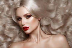 美丽的金发碧眼的女人以与卷毛、自然构成和红色嘴唇的好莱坞方式 秀丽表面和头发 库存图片