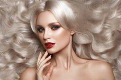 美丽的金发碧眼的女人以与卷毛、自然构成和红色嘴唇的好莱坞方式 秀丽表面和头发 免版税图库摄影