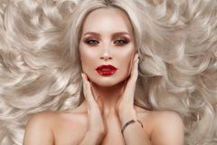 美丽的金发碧眼的女人以与卷毛、自然构成和红色嘴唇的好莱坞方式 秀丽表面和头发 免版税库存照片