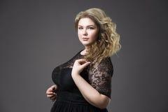 年轻美丽的金发碧眼的女人加上在黑dres的大小模型, xxl在灰色演播室背景的妇女画象 免版税库存照片