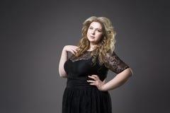 年轻美丽的金发碧眼的女人加上在黑dres的大小模型, xxl在灰色演播室背景的妇女画象 库存图片