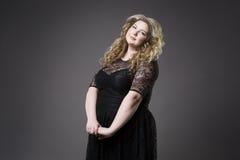 年轻美丽的金发碧眼的女人加上在黑dres的大小模型, xxl在灰色演播室背景的妇女画象 图库摄影